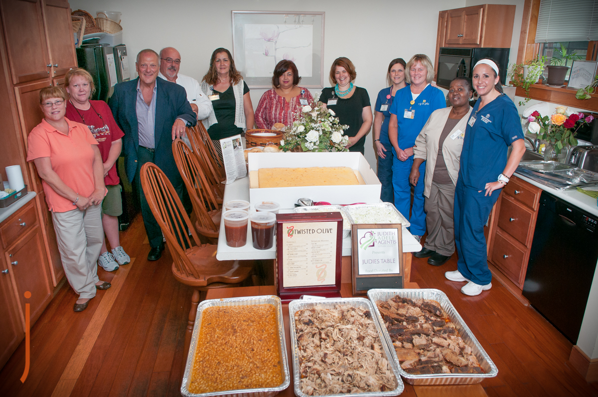 Steve Kershner of the Twisted Olive with Bob Agentis and Staff around Judie's Table at the St Luke's Hospice House